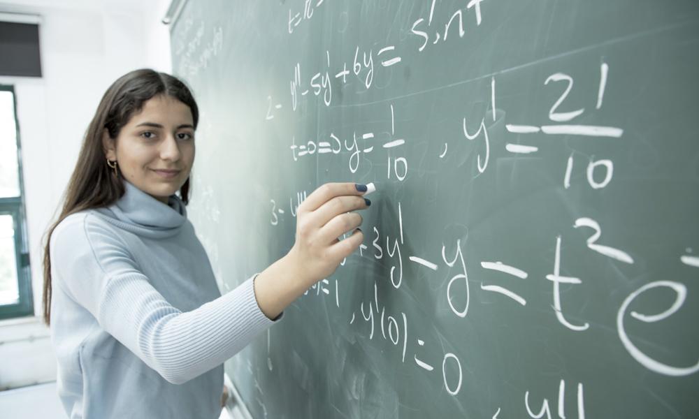 Studentessa scrive equazioni su lavagna